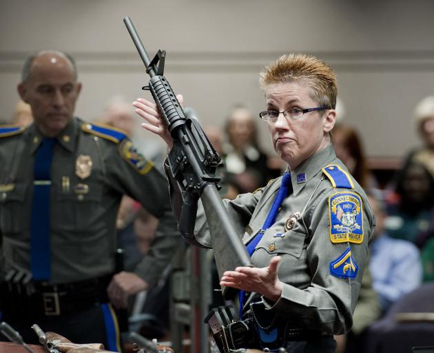Detective Barbara J. Mattson, of the Connecticut State Police, holds a Bushmaster AR-15 rifle, the same make and model used by Adam Lanza in the 2012 Sandy Hook School shooting. Photo: AP