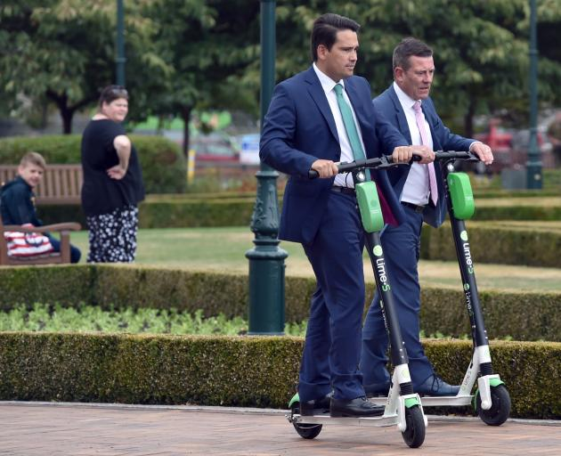 National Party leader Simon Bridges, middle, and Dunedin MP Michael Woodhouse, ride Lime scooters at Dunedin Railway Station yesterday. Photo: Gregor Richardson