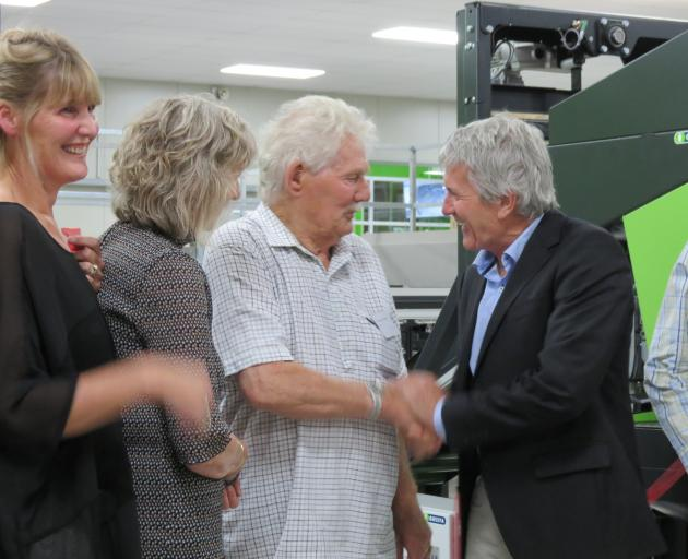 Orchard and packhouse owner Con van der Voort, of Ettrick, is congratulated by Minister of Agriculture Damien O'Connor (right), at the CAJ van der Voort packhouse in Ettrick. Watching the ribbon-cutting are daughter (from left) Jackie van der Voort and To