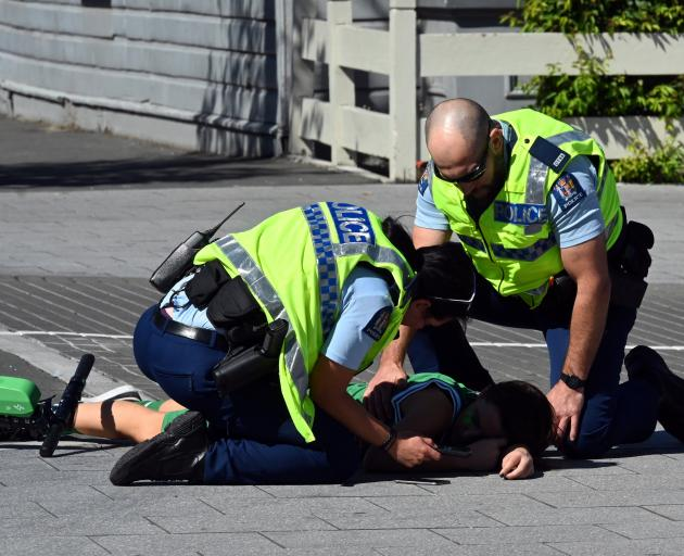 Revellers pour dPolice officers go to the aid of a young man who crashed off a Lime scooter at the corner of Castle and Dundas Sts in North Dunedin own Castle St at the height of the St Patrick's Day festivities yesterday afternoon. Photo: Linda Robertson