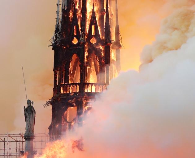 Smoke billows as fire engulfs the spire before it collapsed. Photo: Reuters