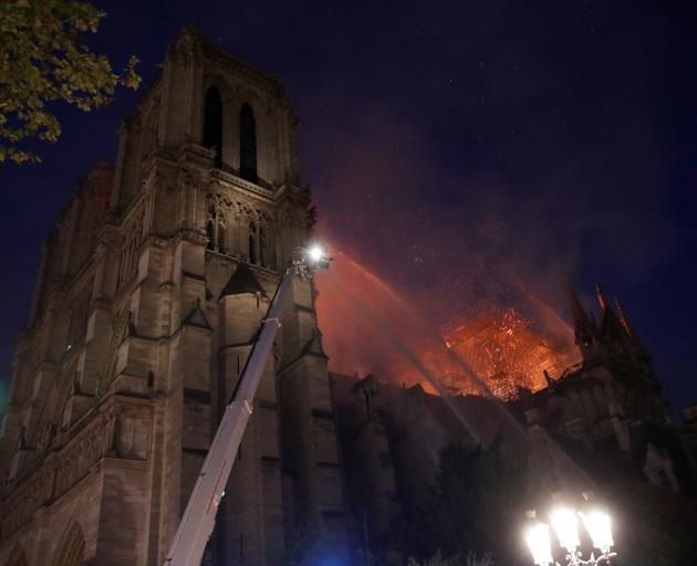 Paris Fire brigade members spray water to extinguish flames as the Notre Dame Cathedral burns in...