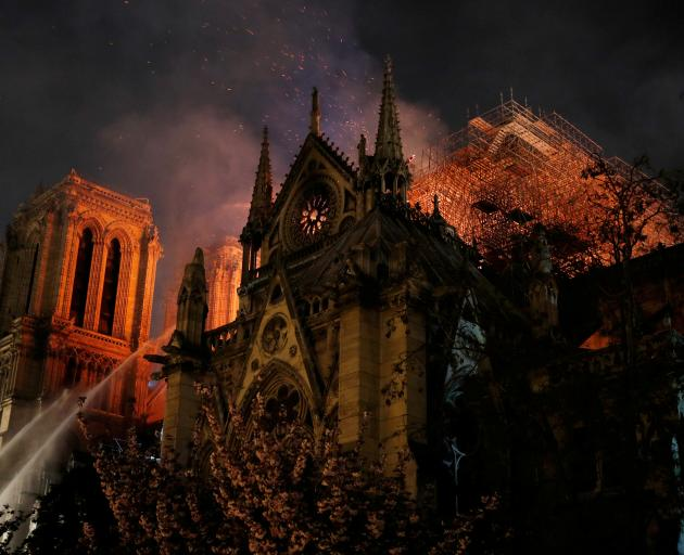 Sparks fill the air as Paris Fire brigade members spray water to extinguish flames as the Notre Dame Cathedral burns in Paris. Photo: Reuters