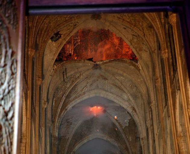 Flames and smoke are seen as the interior continues to burn inside the Notre Dame Cathedral in...