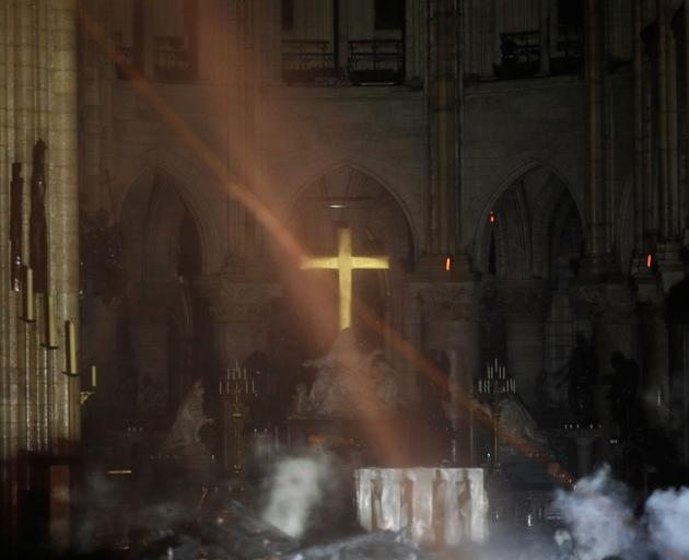 Smoke rises around the alter in front of the cross inside the Notre Dame Cathedral as a fire...