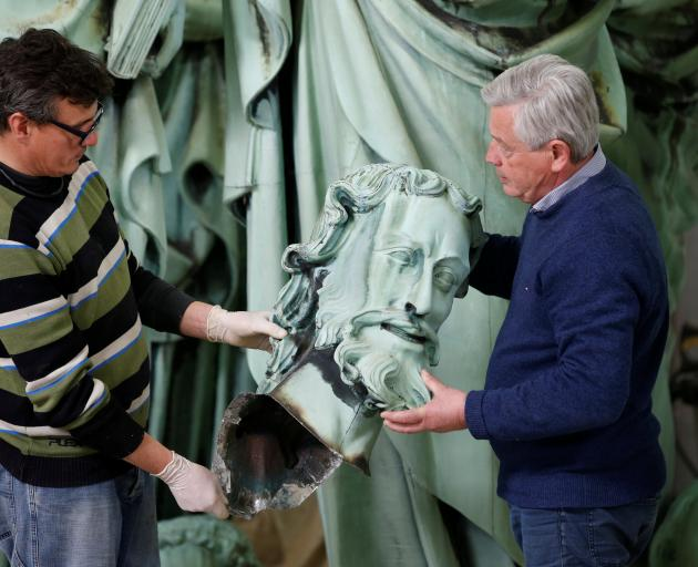 Consultant Patrick Palem (right) checks statues that were removed from the spire of Paris' Notre...