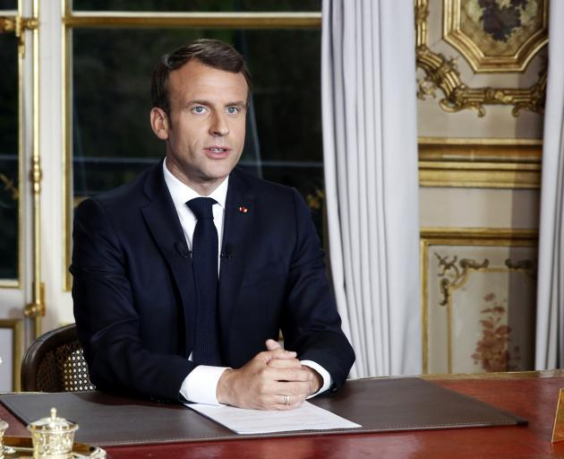 French President Emmanuel Macron addresses the French nation following a massive fire at Notre...