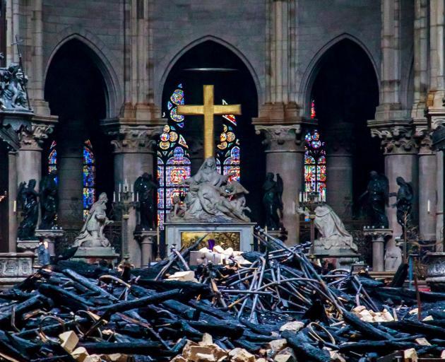 A view of the cross and sculpture of Pieta by Nicolas Coustou in the background of debris inside Notre-Dame de Paris. Photo: Reuters