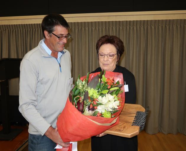 Sue Edgerton accepts her late husband Ewen 'Uge' Edgerton's posthumous life membership from Jim O'Malley. Photo: Mountain Scene