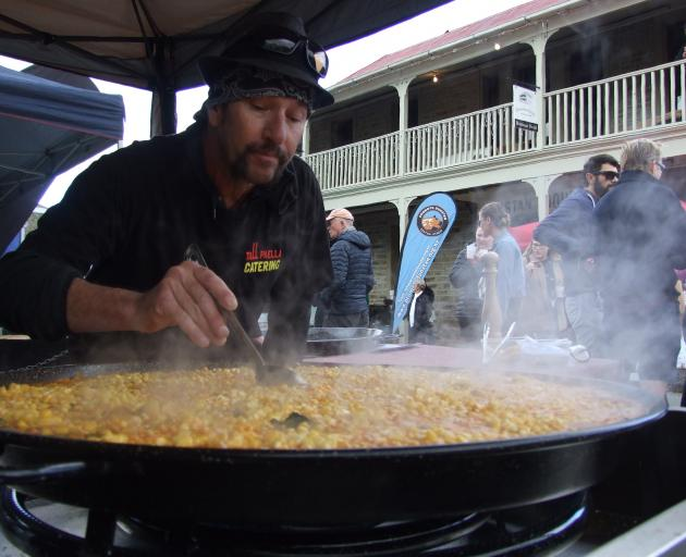 Dean Perkins, of Gore, prepares some Spanish chicken and sweetcorn paella at yesterday's Clyde...