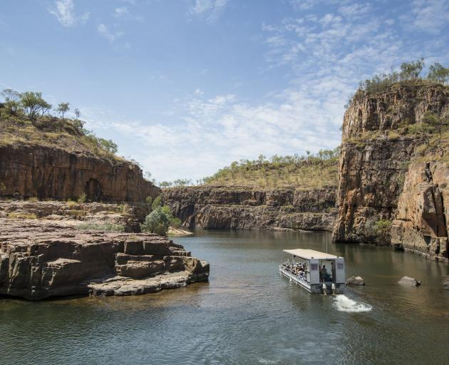 A tourist boat travels through the Nitmiluk Gorge, near Katherine, during a Ghan off-train...