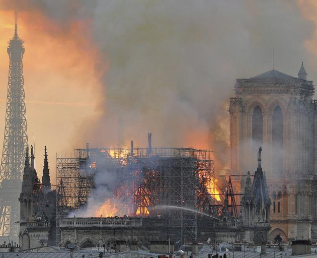 Flames and smoke rise from the blaze after the spire toppled over on Notre Dame cathedral in...