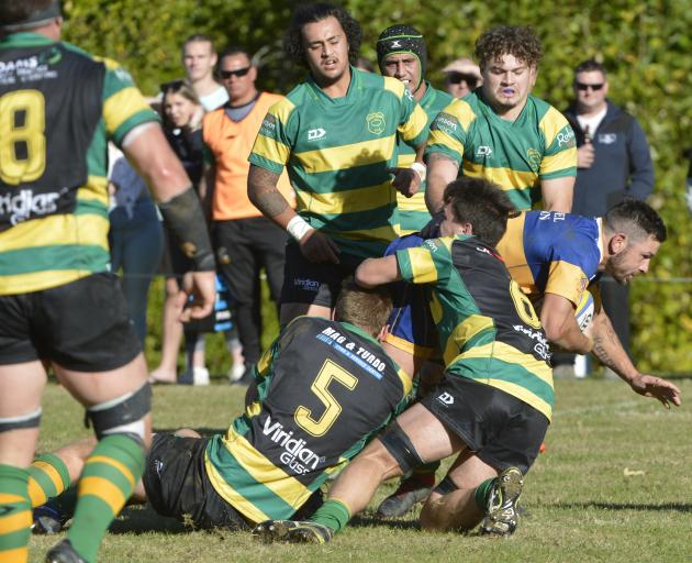 Green Island players combined to tackle Taieri midfielder Kori Rupene at Miller Park on Saturday....