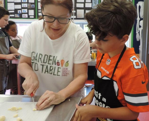 Linda Taylor shows Jack Brosta (9) how to slice garlic.
