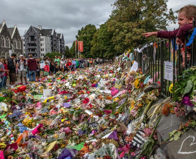 A boy points over flowers and tributes during a march to remember victims of the Christchurch...