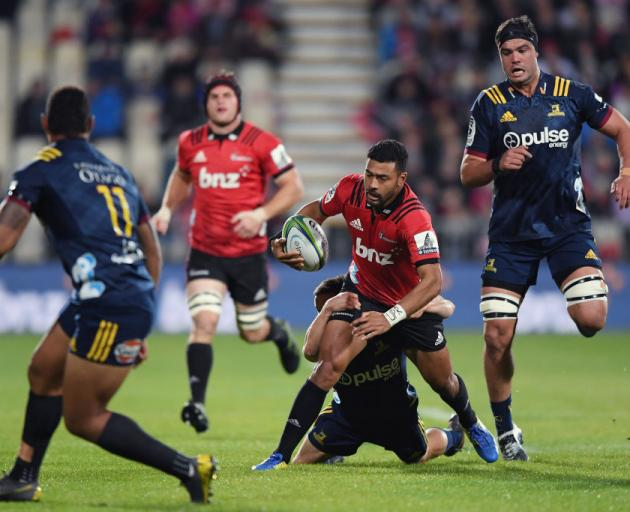 Richie Mo'unga is tackled while running the ball for the Crusaders against the Highlanders...