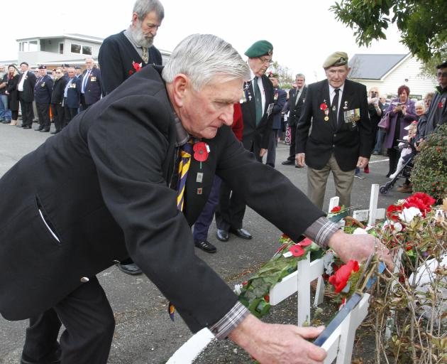 Watched by other veterans, Private Pat Blair, a veteran of Malaya and Vietnam, lays a wreath at...