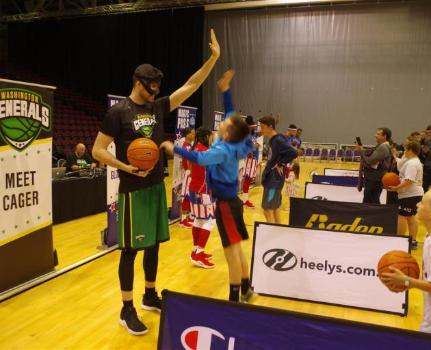 Kai Ladbroke (12), of Invercargill, jumps as high as he can to high-five the 2.32 m tall Paul ``Cager'' Sturgess who played for the Washington Generals against the Globetrotters last night. Basketball enthusiasts got to meet the Globetrotters at ILT Stadi