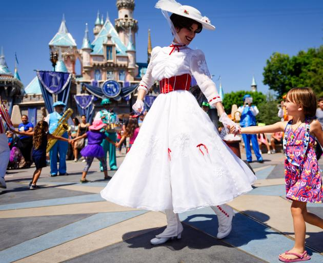 Mary Poppins leads a line of children in song and dance in front of Cinderella's castle.