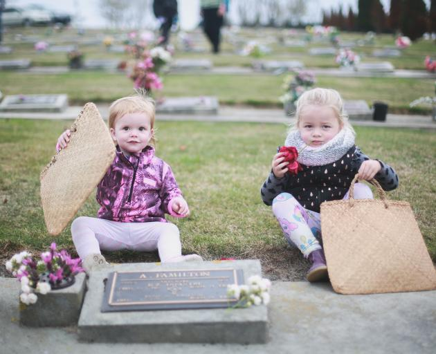 Peyton McAuley (left, 1) and Chloe Angland (3), from Barnardos Home-based early learning, place posies at the grave of A. Familton, who is buried in the services section of the Oamaru Cemetery, as part of an annual children's posy-laying ceremony yesterda