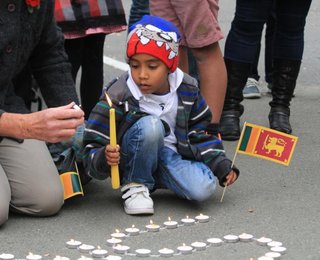 Chathushka Pitiwila Liyanage (6), of Oamaru, lights candles at a vigil for the more than 250 people killed in the Easter Sunday terrorist attacks in the country where he was born.  Photo: Hamish MacLean