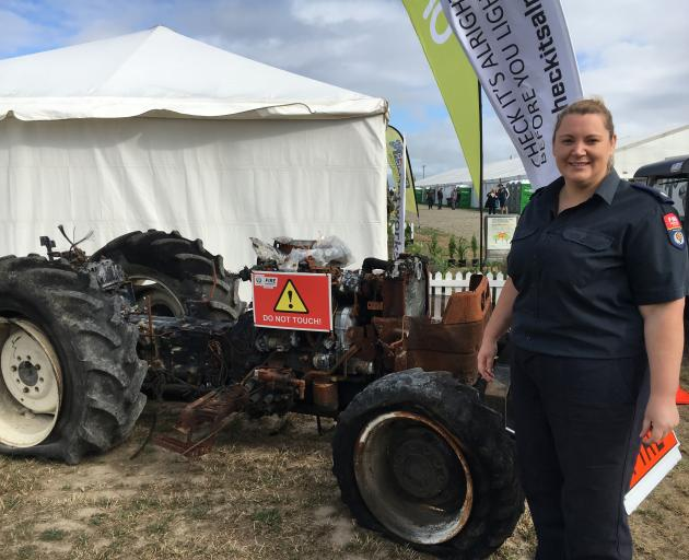 Fire and Emergency New Zealand fire risk management officer Kerri Pring displays a burnt-out tractor at South Island Agricultural Field Days last month. Photo: David Hill