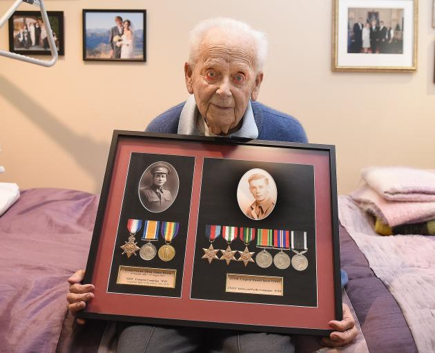 Russell Towns holds a framed display of medals won by his father Alfred in World War 1 and by him in World War 2. Photo: Gregor Richardson