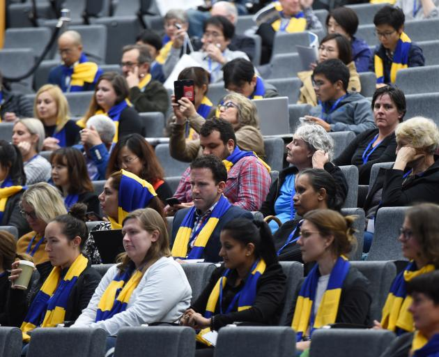 The audience listens intently to the conference