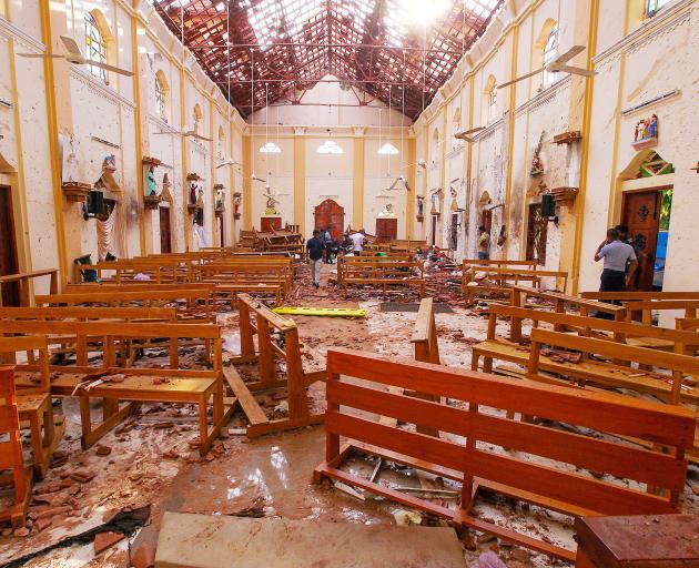 Crime scene officials inspect the site of a bomb blast inside St Sebastian's Church in Negombo....