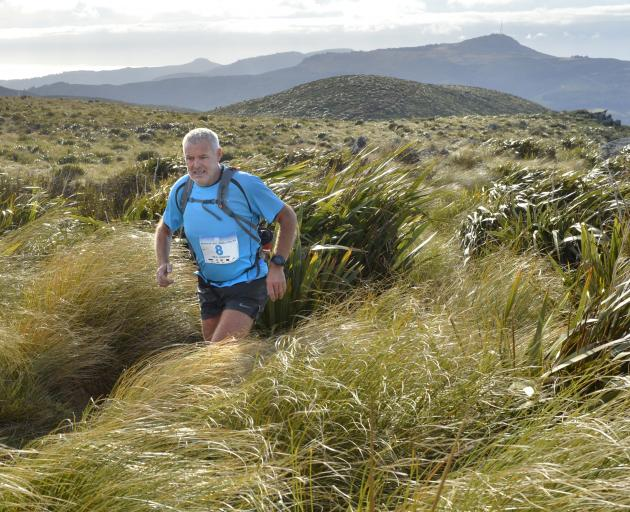 Masters runner Neal Gordon battles high winds as he nears the summit of Flagstaff during the...