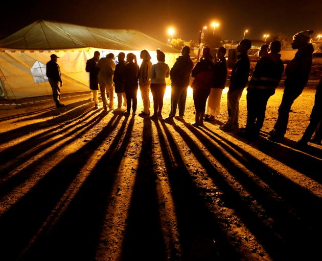 Voters queue to cast their ballots before polls close outside a polling station in Alexandra...