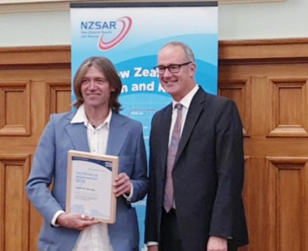 LandSAR Wanaka alpine cliff rescue team leader Davie Robinson receives a certificate of achievement award from Transport Minister Phil Twyford for his team's efforts in the rescue. Photo: Jon McQueen
