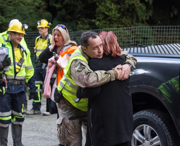 Anna Osborne is embraced by Pike River Recovery Agency member Karl Maddaford, while Mr Pattinson...