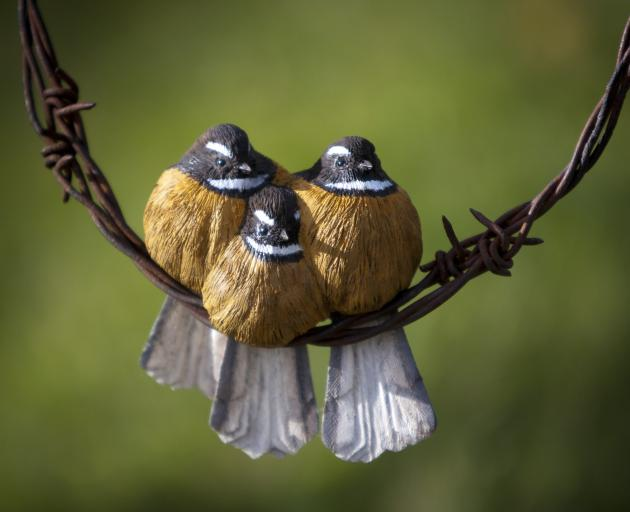 Baby fantails carved from kauri huddle on barbed wire. PHOTO: ERIC SCHUSSER