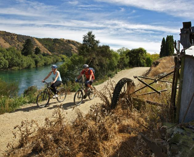 Cyclists travel alongside the Clutha Gold Trail.
