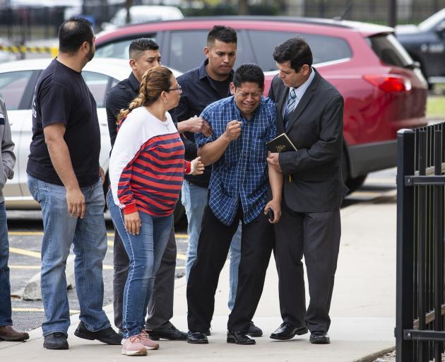 Arnulfo Ochoa is surrounded by family members and supporters, as he walks into the Cook County medical examiner's office to identify his daughter's body. Photo: Chicago Sun-Times via AP
