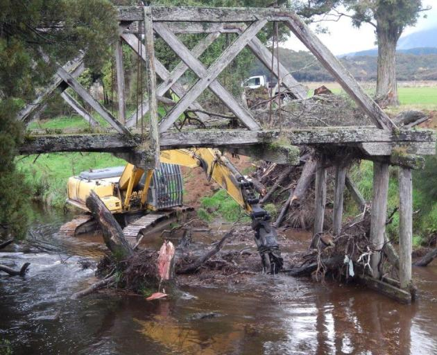 Otago Regional Council contractors remove a log from the Sir Truby King bridge in Tahakopa earlier this month. Photo: Don Sinclair/Supplied