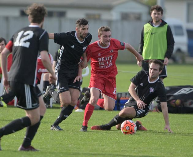 Caversham's Connor Neil (in red) contests the ball with Northern Hearts player Sullivan Martin in...