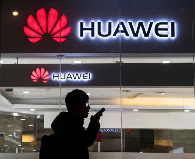 A pedestrian talks on the phone while walking past a Huawei Technologies Co. store on January 29, 2019 in Beijing, China. Photo: Getty Images