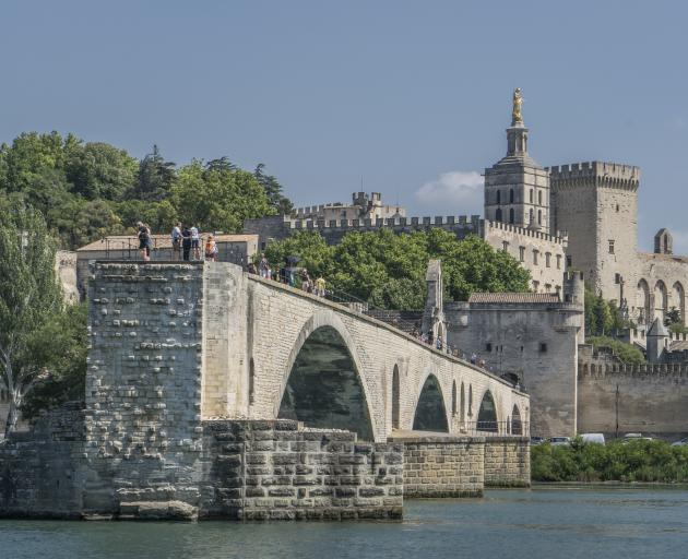 Avignon is encircled by a 4km wall complete with parapets and towers and the Medieval Pont Saint-Benezet bridge. Photo: Getty Images