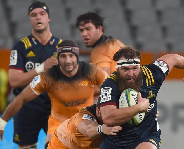 Liam Coltman pins his ears back to make a run for the Highlanders as Jaguares hooker Julian...