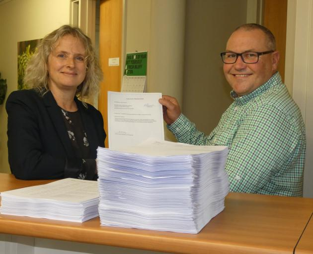 Labour MP Dr Liz Craig is presented with a petition submission from Karl Thomas yesterday in...