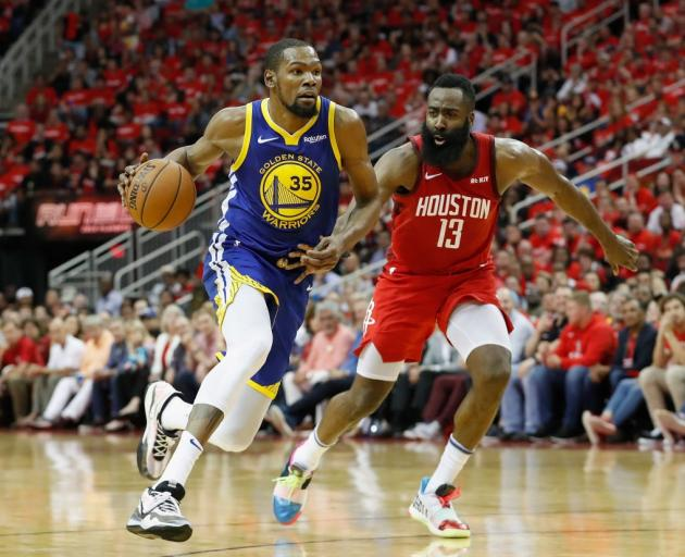 Kevin Durant drives to the hoop against James Harden during the NBA's western conference...