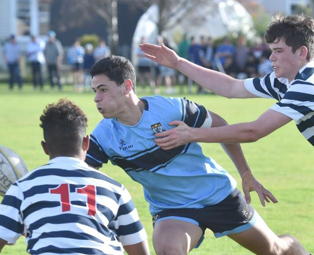King's High School first XV midfielder Ryan Jones looks to move the ball on despite the attention...