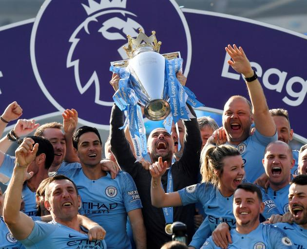 Manchester City manager Pep Guardiola lifts the trophy as they celebrate winning the Premier League. Photo: Reuters