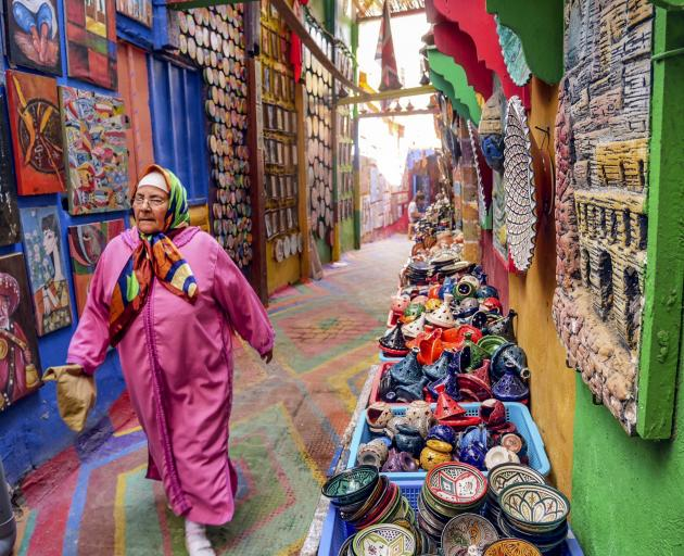 A woman walks down a brightly painted alley in Fez.