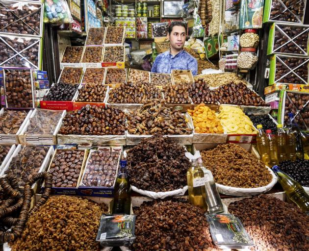 A man sells dates and other dried fruits in one of the thousands of stalls in the souks of Fez.