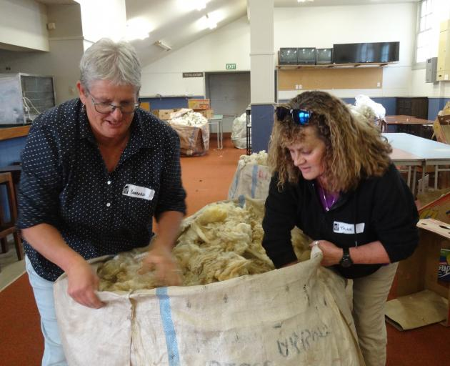 Wool classers Barbara Newton (left), of Dunedin, and Trudi Landreth of Whakatu, Hawke's Bay, load wool after a competition at the annual meeting.