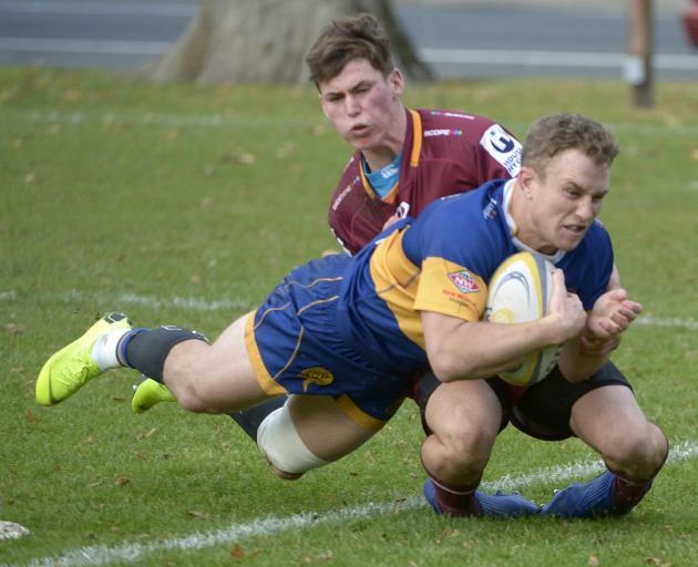Taieri outside back Mitchell Scott scores despite the best efforts of Alhambra-Union fullback...