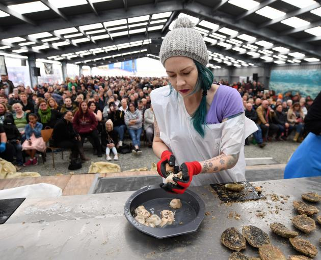 Melisa Matheson-Calders competes in the novice oyster opening race in front of a packed tent at...